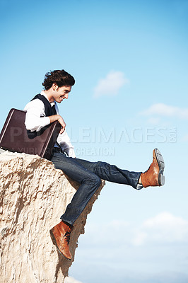 Buy stock photo Young man with a briefcase sitting with his legs dangling over a cliff and smiling