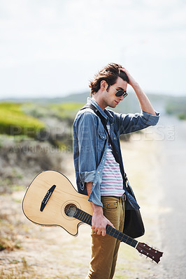 Buy stock photo Trendy young man holding an acoustic guitar standing on the side of the road