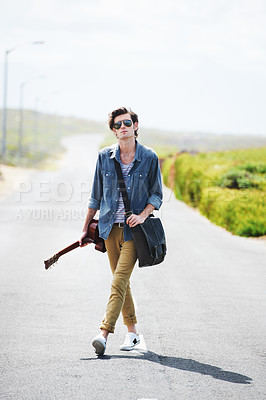 Buy stock photo Trendy young male wearing sunglasses standing in the middle of the road holding a guitar