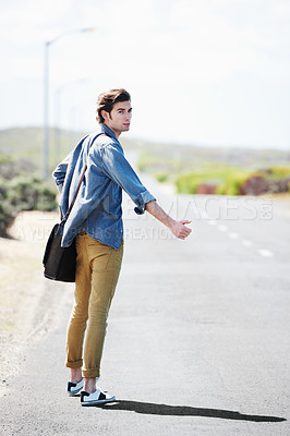 Buy stock photo Handsome young man hitchhiking on the side of the road