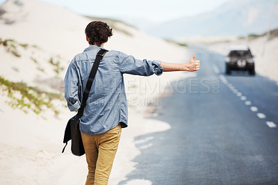 Buy stock photo Rear-view of a trendy young man hitchhiking on the side of the road with a car in the distance