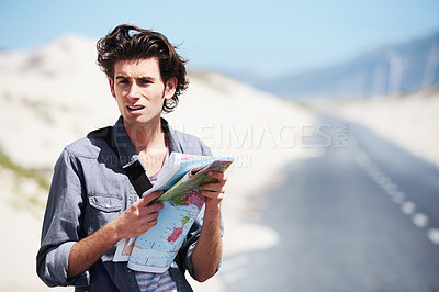Buy stock photo Trendy young man standing on the side of the road holding a map and looking puzzled