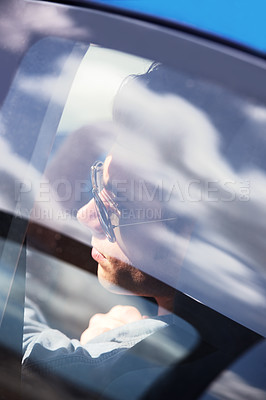 Buy stock photo Closeup of a young male wearing sunglasses seen through the window of a car