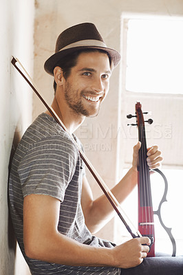 Buy stock photo Handsome young musician holding his violin on a stairwell