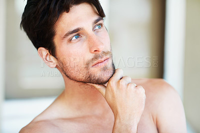 Buy stock photo Handsome young man holding his chin in contemplation
