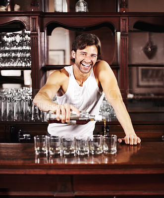 Buy stock photo Handsome young barman pouring drinks out into glasses on the counter