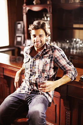 Buy stock photo Attractive young guy perched at a bar counter with a drink in hand