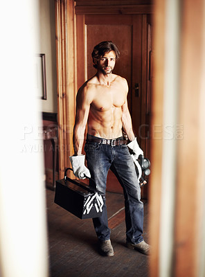 Buy stock photo Attractive young handyman standing shirtless while holding his tools