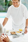 Happy old man serving a woman with healthy breakfast in bed