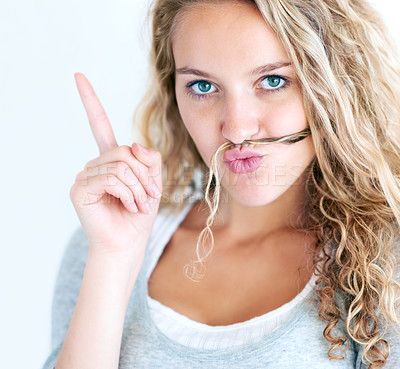 Buy stock photo A brash pretty blonde with her hair on her lips pointing upwards