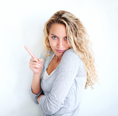 Buy stock photo A naughty, vivacious blonde looking at you and pointing away