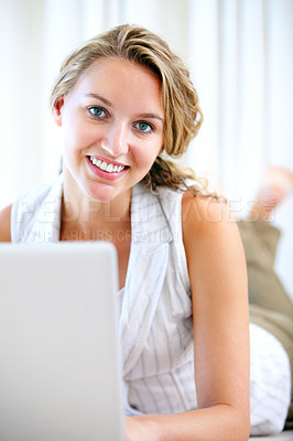 Buy stock photo Portrait of a beautiful young blonde working on a laptop while relaxing on the floor