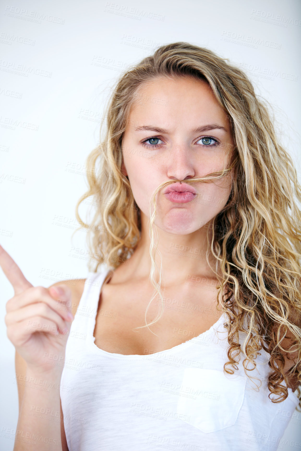 Buy stock photo A young beauty fooling around by putting her hair on her upper lip and pouting while pointing