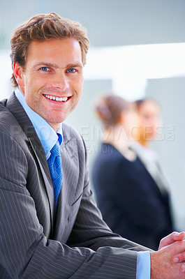 Buy stock photo Young and handsome businessman with his colleagues in the background
