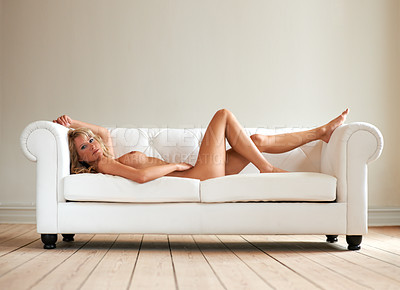 Buy stock photo Gorgeous naked woman reclining on a white sofa