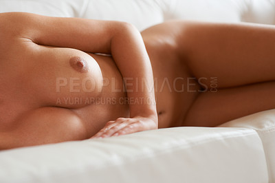Buy stock photo Cropped view of a curvaceous naked woman lying on a sofa