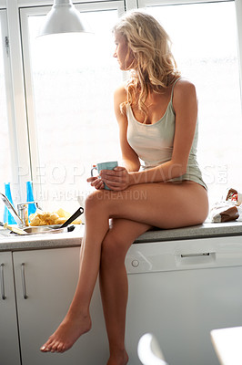 Buy stock photo Attractive young woman seated on her kitchen counter in her nightwear and having a cup of coffee