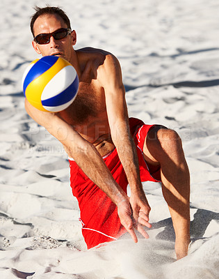 Buy stock photo A young man playing volleyball at the beach
