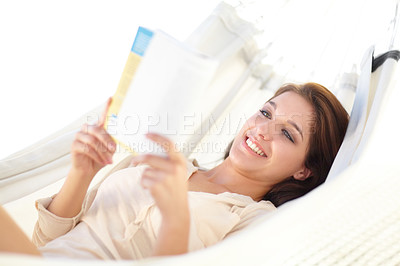 Buy stock photo A beautiful young woman relaxing in a hammock reading a book