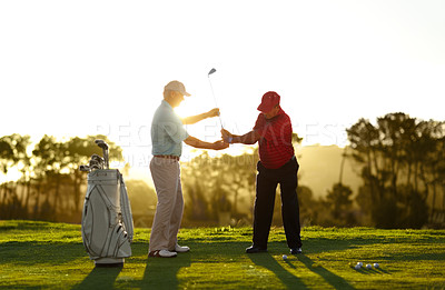 Buy stock photo A male golfer receiving help from his caddy on the golf course