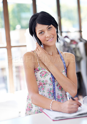 Buy stock photo Portrait of an attractive young ethnic woman making appointments via cellphone