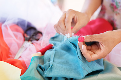 Buy stock photo Closeup image of a woman's hands sewing a button to a garment at work