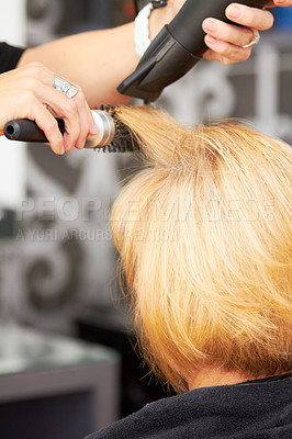 Buy stock photo A blonde woman getting her hair blow dried at the hairdresser