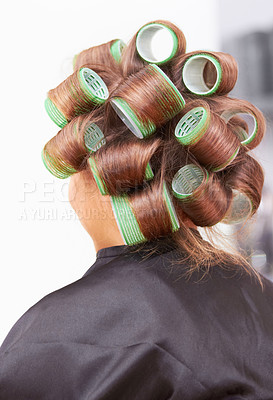 Buy stock photo Rear view of a woman with rollers in her hair at the hairdresser