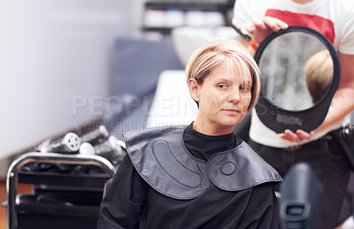 Buy stock photo A woman examing her haircut in the mirror at the hairdresser