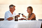 Romantic mature couple drinking wine in the beach during sunset