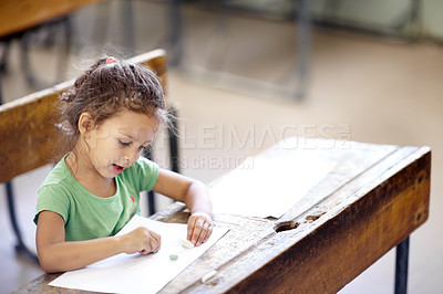 Buy stock photo Cute little girl sitting at a school desk and drawing