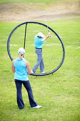 Buy stock photo Image of a male coach instructing his female student using a ring to adjust and correct her swing