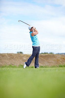 Buy stock photo A young woman following through after driving the ball down the fairway