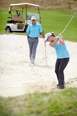 Buy stock photo A young female golfer chipping her ball out of a bunker while her male partner looks on from behind