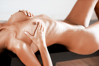 Buy stock photo Cropped view of a sensual nude woman lying on top of a table while holding her breasts