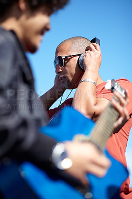 Buy stock photo Shot of a young man playing the guitar while his friend uses his his headphones