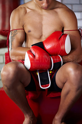 Buy stock photo A young shirtless fighter sitting while wearing his boxing gloves