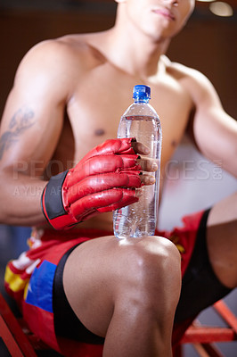 Buy stock photo Cropped image of a young boxer sitting with a bottle of water in his hand