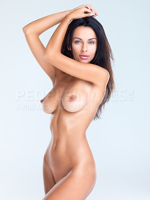 Buy stock photo A side view studio shot of a beautiful naked model with her arms resting on the top of her head