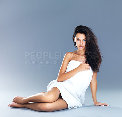 Buy stock photo A studio shot of an attractive model lying down on the floor and resting on one arm while wrapped in a white towel