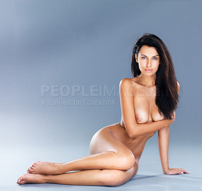 Buy stock photo A studio shot of a beautiful naked model lying on the floor leaning on one arm