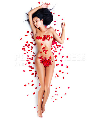 Buy stock photo A full length high angle shot of an attractive naked female model covered in rose petals