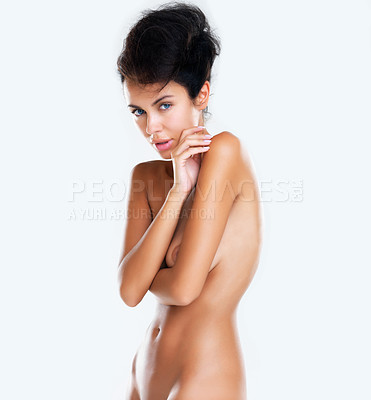 Buy stock photo A studio shot of an attractive naked model looking at the camera with her arms crossed isolated on a white background