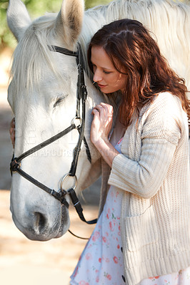 Buy stock photo A beautiful woman standing close to her horse outside