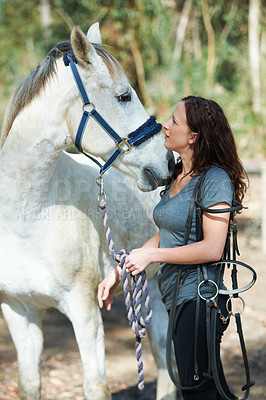 Buy stock photo An attractive woman outside holding a bridle while looking at her horse
