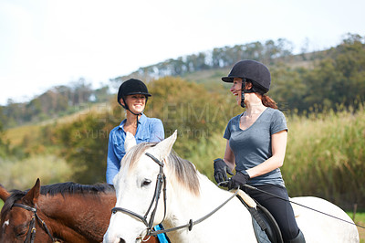 Buy stock photo Two young women talking while horseback riding