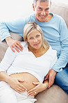 Happy mature pregnant woman with her husband relaxing on couch