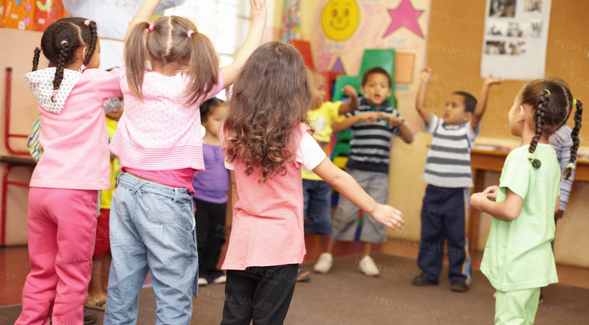 Buy stock photo Preschool students jumping and dancing around having fun