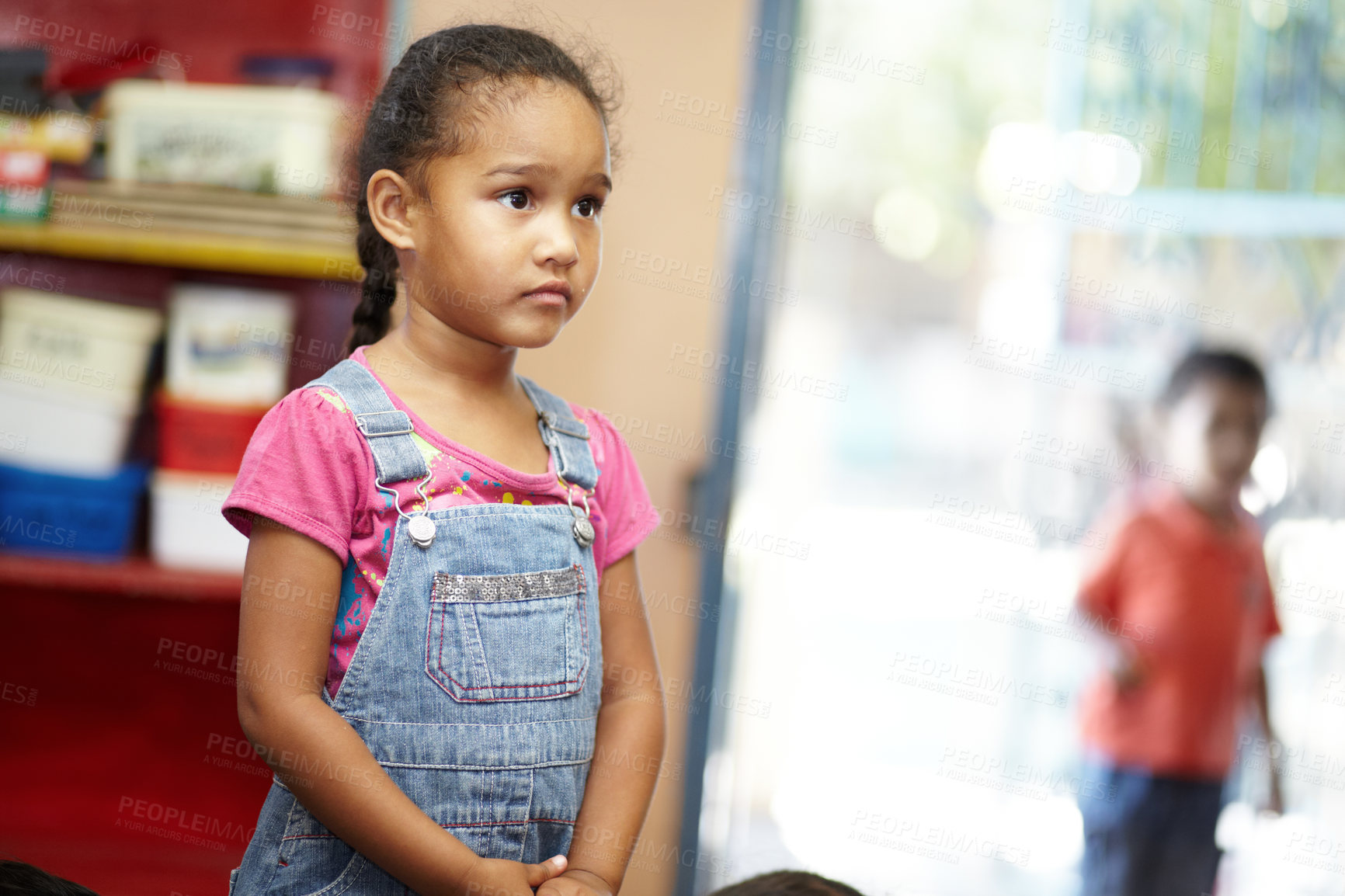 Buy stock photo A small cute pre-school girl looking at something off camera and seems to be lost in thought in her pre-school classroom