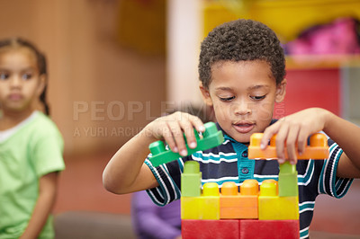 Buy stock photo An interested pre-school child building something with plastic blocks